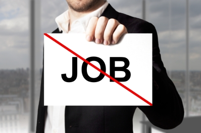 businessman in black suit holding sign job crossed out jobless