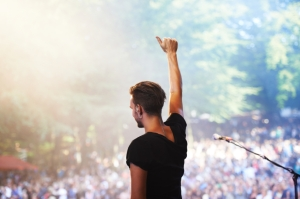 A performer standing on stage facing the crowd with his hand in the air